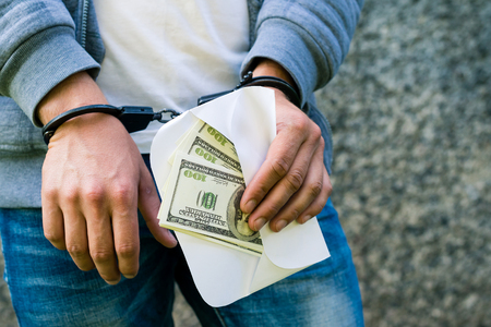 arrested rowdy in handcuffs with dollars money in the envelope.
