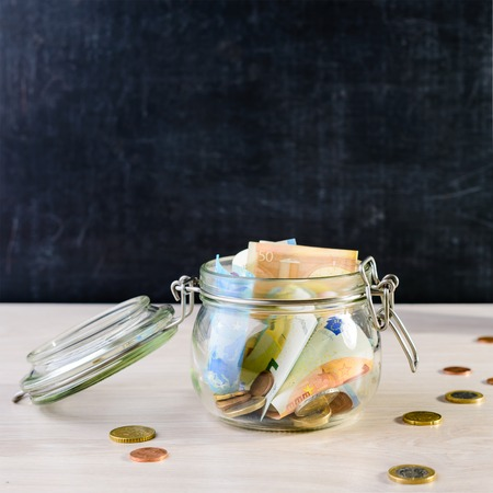 Coins and paper money in a glass jar on wooden table against dar