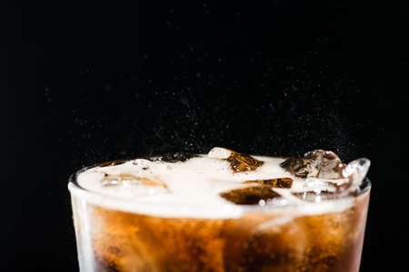 Ice cola with splashing CO bubbles in a glass