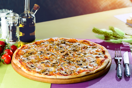 Appetizing pizza with mushrooms, meat, cheese, sauce and herbs o