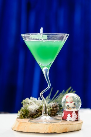 Martini glass with Christmas green cocktail on blue background Stock Photo
