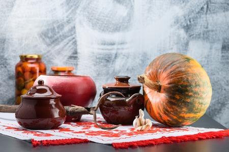 Nature morte avec pots de nourriture, citrouille et ail sur une table. Tradi Banque d'images