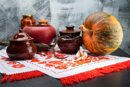 Still life with food pots, pumpkin and garlics on a table. Tradi