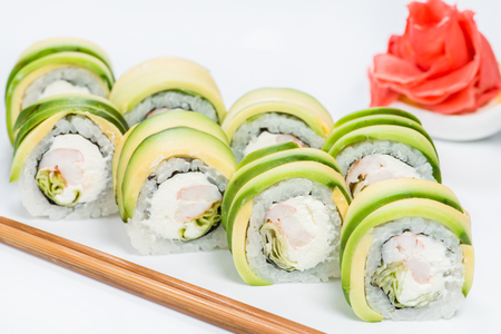 Delicious Philadelphia sushi rolls with rice, avocado, cream cheese and salmon on light background