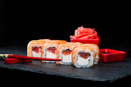 Traditional Japanese cuisine. Selective focus on set of sweet sushi rolls with salmon, cream cheese, rice and raspberry on dark background 免版税图像