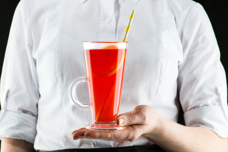 The unidentified waiter brings a hot cranberry tea cocktail with lemon and cinnamon