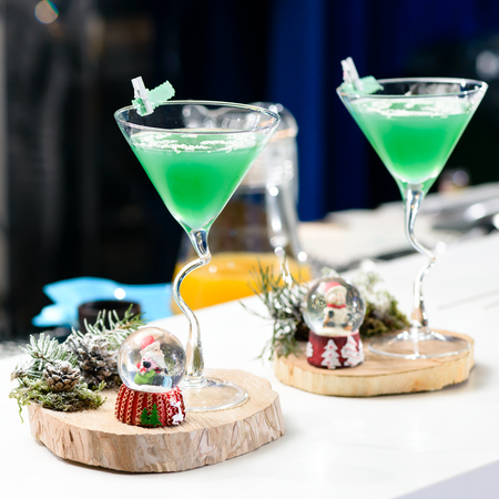 Two martini glasses with Christmas green cocktail, shallow dof