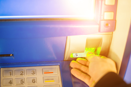 Hand inserting ATM card into bank machine