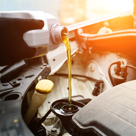 Fresh oil being poured during an oil change to car engine in ray