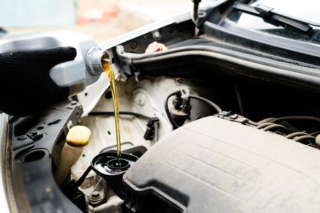 Se vierte aceite nuevo durante un cambio de aceite en el motor del automóvil, cierre