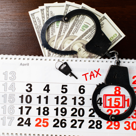 steel police handcuffs, dollars money,  April 15 on calendar and Tax word on wooden background, top view. National Tax Day and financial concept 写真素材