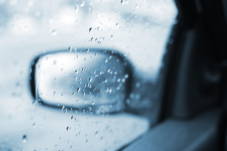 Raindrops on the car rearview mirror, selective focus Banco de Imagens