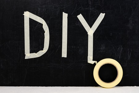 top view of word DIY made with adhesive tape on dark background, near laying sticky tape Stock Photo