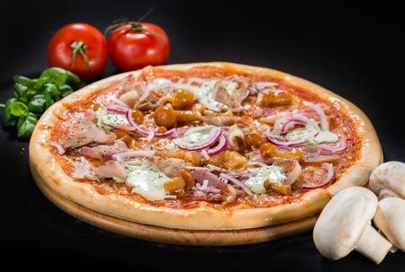 Delicious hot Mushroom Pizza with mozzarella, bacon, champigon, onion, pepper and sauce on wooden round board on dark background