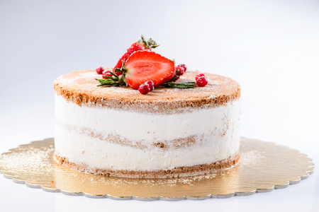 Delicious sweet cake with powdered sugar and strawberries on light background Stock Photo