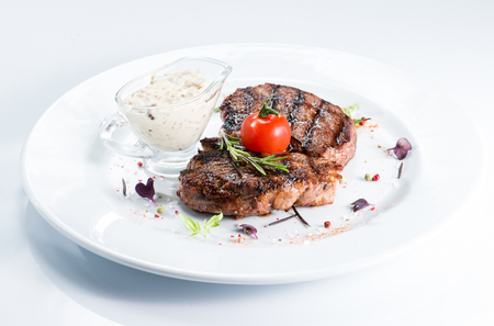 Grilled steak delicious beef meat on a white plate on a light background menu Stockfoto