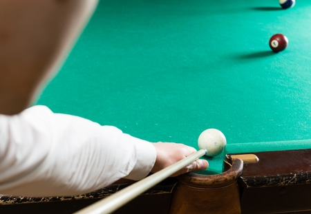Billiards pool game, athlete with cue close-up, selective focus Stock Photo