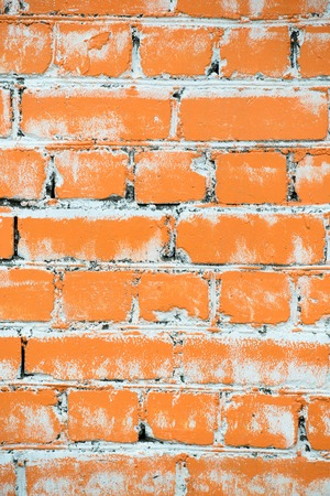 Texture of a brick wall painted with orange paint close-up