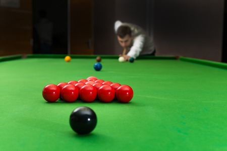 Game snooker billiards, athlete kick cue close up, selective focus