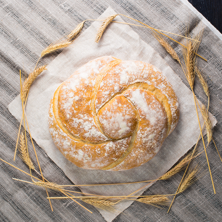 still life with delicious baked good on a light textile background. Flat lay, capital bun