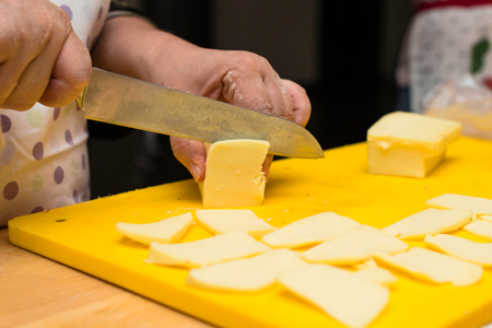 woman hands slices cheese to make an Italian pizza
