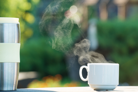 Cup of coffee or tea with steam and thermos on natural abstract