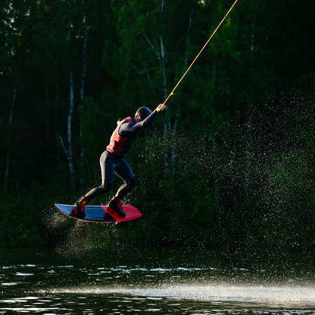 man making trick in jump time with wakeboard On the lake