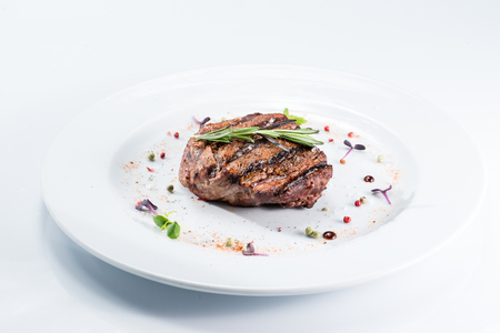 Grilled steak delicious beef meat on a white plate on a light background menu Foto de archivo
