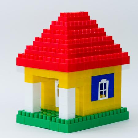 buntes Haus gemacht von Kinderkonstrukteur auf abstraktem Hintergrund