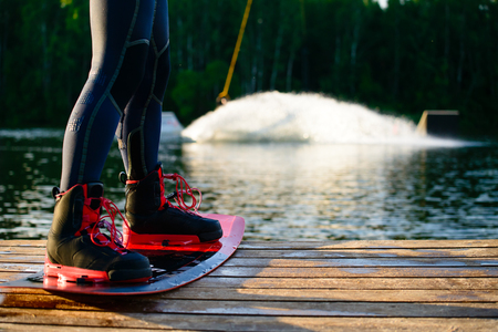 men s feet on a wakeboard on forest landscape