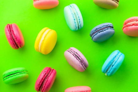 colorful macaroons scattered in different direction on green background, flat lay