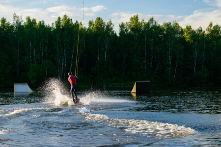man to ride a wakeboard on forest landscape