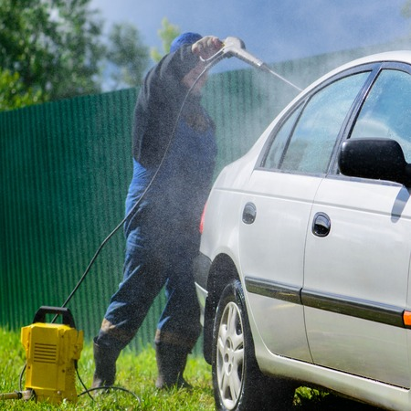 Unidentified man worker washing car under high pressure water ou