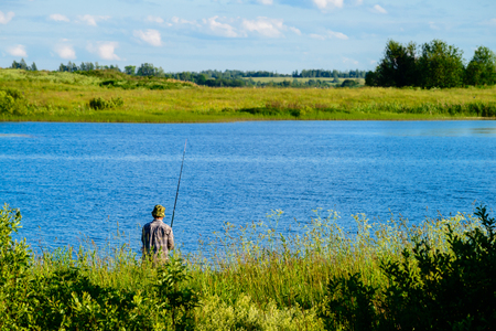 Unidentified man fishing on the lake on summer day