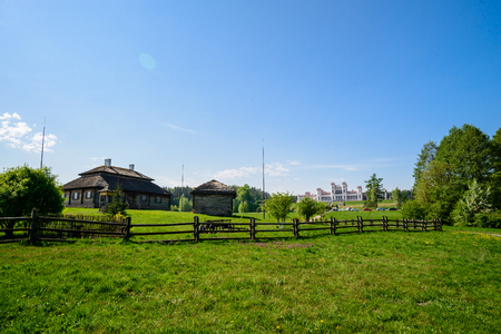 Beautiful amazing summer landscape of Russian village. Old wooden houses in the meadow on summer day