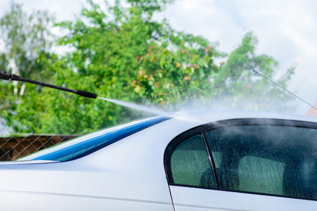 Unidentified man worker washing car under high pressure water outdoors. Cleaning automobile