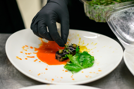 Chef serves a dish with tongue and salad in the kitchen of the restaurant