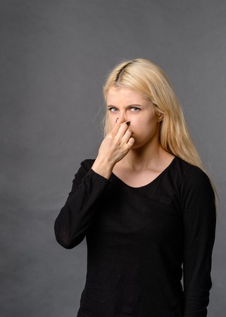 girl gesture smells bad Bad smelling concept. Studio shot of disgusted young European woman pinching her nose because of awful stink coming out from garbage or spoiled food. Negative human emotions