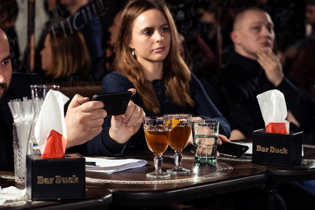 Cocktail bars, competition of bartenders, a jury of a girl and a man tasting a new alcoholic cocktail February 6th Bartenders Day Minsk, toned, Belarus, 2019