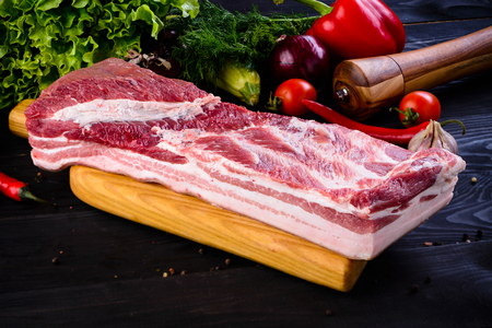 Raw pork meat. Fresh steaks tenderloin on wooden cutting board on dark background. Raw belly with vegetables and Spices
