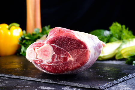 Raw fresh meat lamb knuckle mutton saddle on stone slate plate. Copy space for Text Stok Fotoğraf