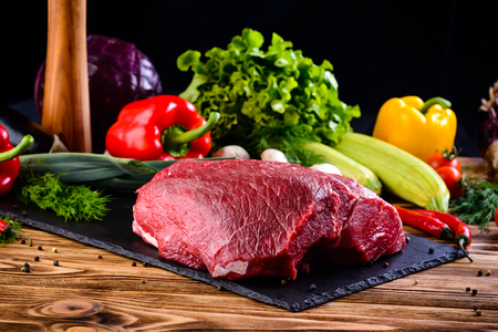 Still life fresh raw beef meat steak on a cutting board with ingredients for cooking on dark table. Top view copy space. Raw beef thick rib, tenderloin and shoulder blade