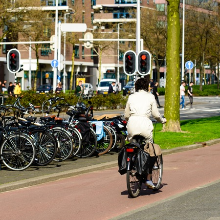 woman rides a bike on a bike path, Amsterdam is a symbol of cycling