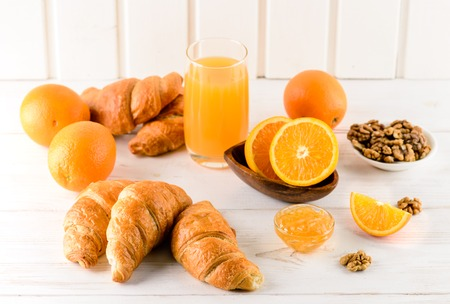 breakfast of oranges and orange juice with fresh croissants on a white wooden table, place for design copy space