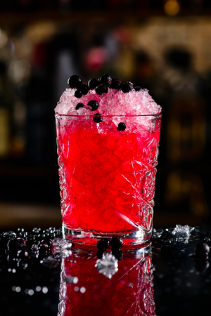 blackcurrant cocktail with ice on a forward bar background