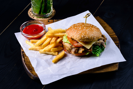 grilled chicken and french fries burger on a black table in a bar and mojito cocktail