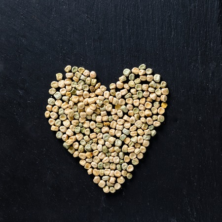 microgreen peas grain and germinated sprout heart concept on adark background with copy space