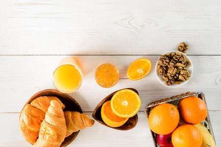 breakfast mockup oranges and croissants on a white wooden table, place for design copy space top view flat lay