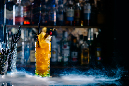 Lemonade with pineapple exotic alcoholic cocktail daiquiri with pineapple in the bar with smoke copyspace