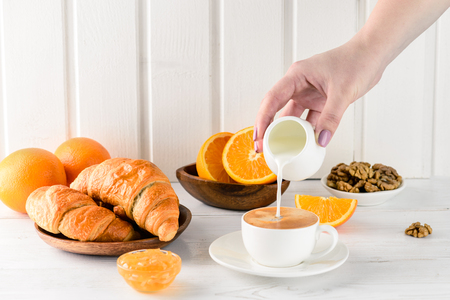 Coffee white cup, croissants breakfast on white background, selective focus. Breakfast concept, female hand pours cream into coffee